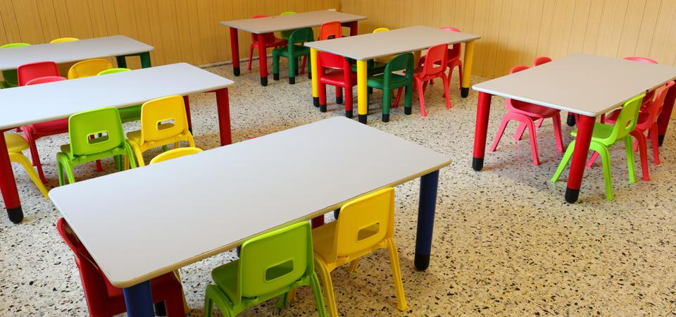 Tables and chairs in an empty elementary school classroom
