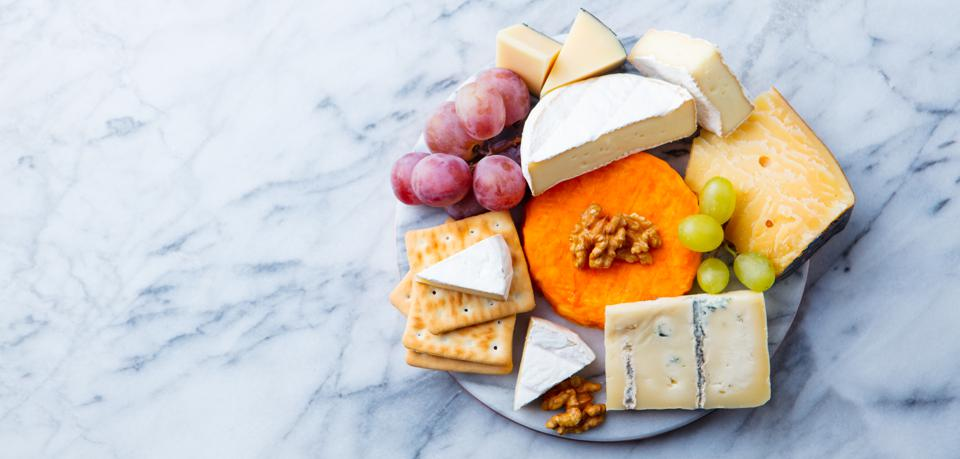 Assortment of cheese, grapes and crackers. Marble background. Top view. Copy space.