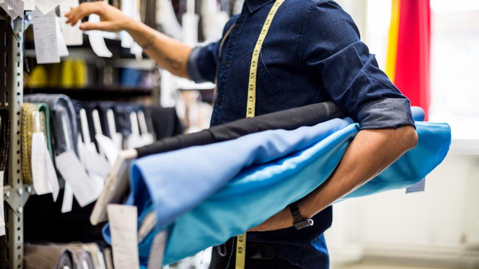 Cropped photo of a male Fashion designer picking out fabric rolls from a display rack.