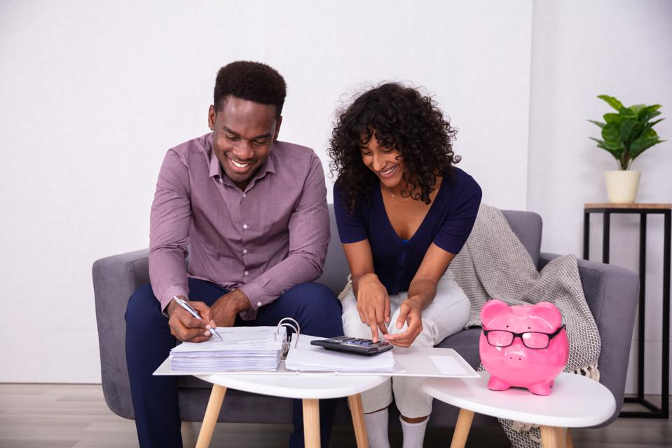 Young couple sitting on sofa discussing finances