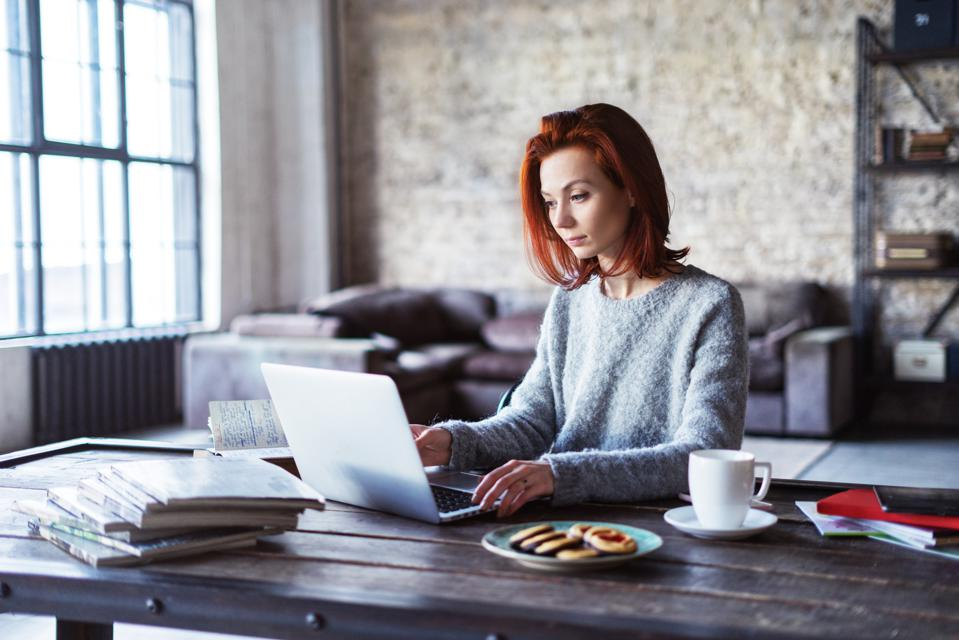 Young woman working in a loft apartment with a laptop computer
