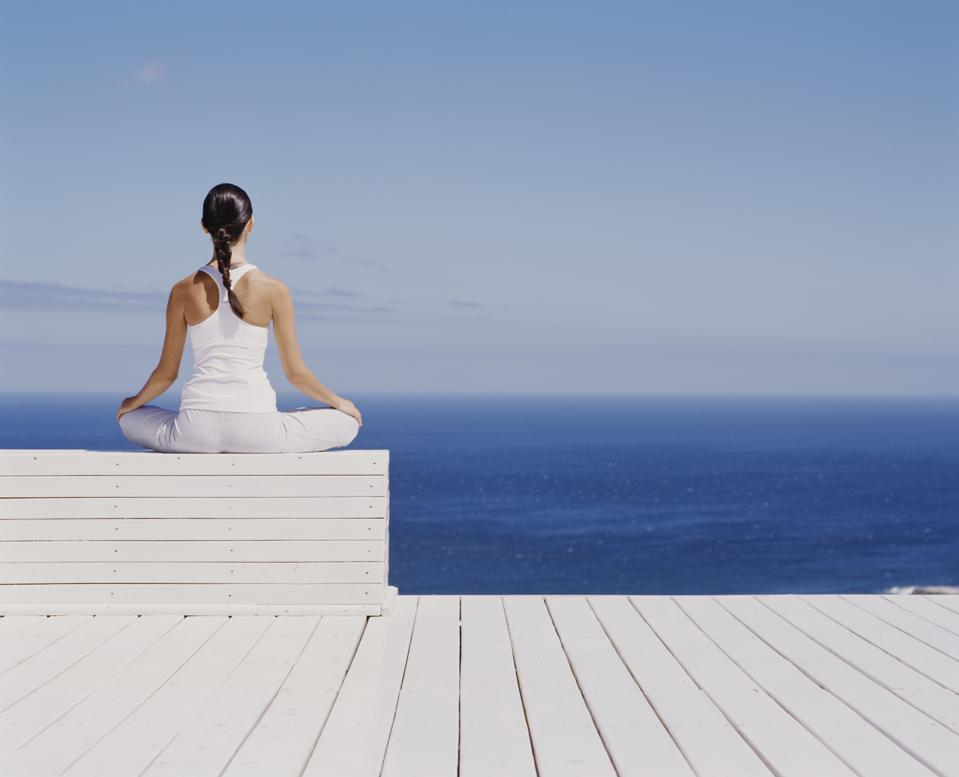 Young woman meditating on wooden block, rear view