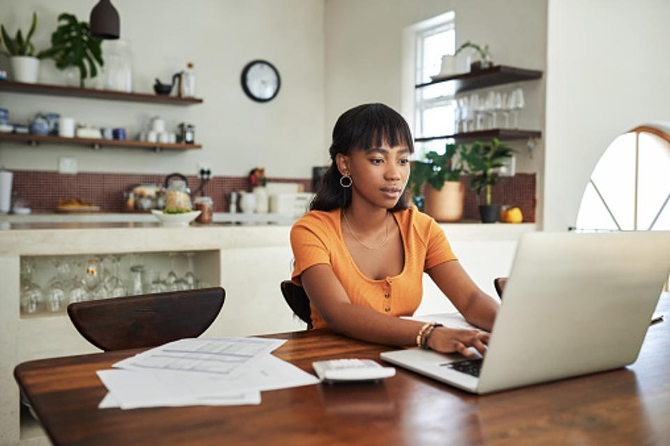 A woman sitting at a kitchen desk and doing work on the computer.