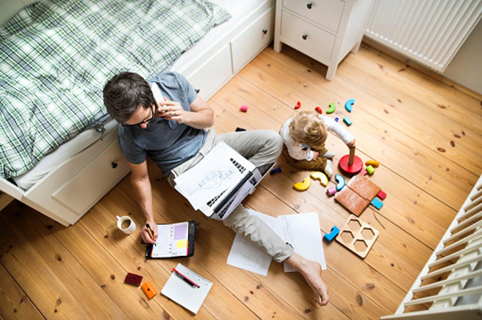 Man working at home with his child next to him.