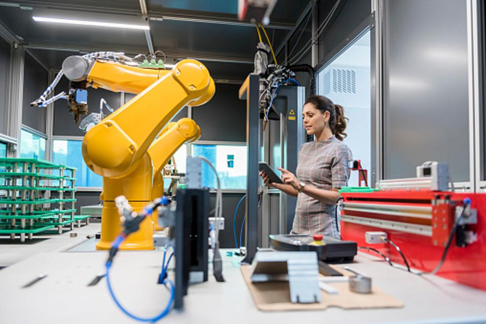 A female engineer working in a machine factory.