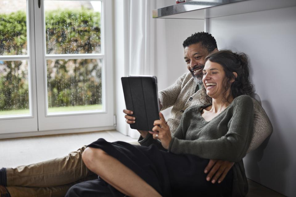 Happy mature man and young woman sitting on the floor using tablet. We are trying to substitute physical experiences for virtual ones.