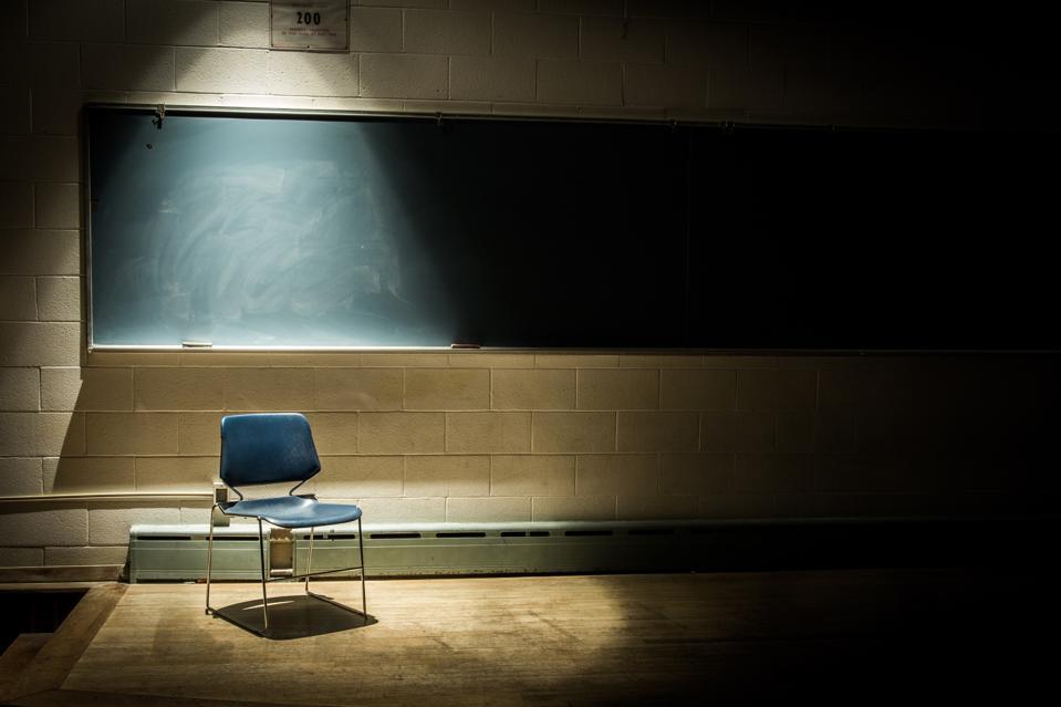 An Empty School Chair in a Dark, Shadowy Classroom