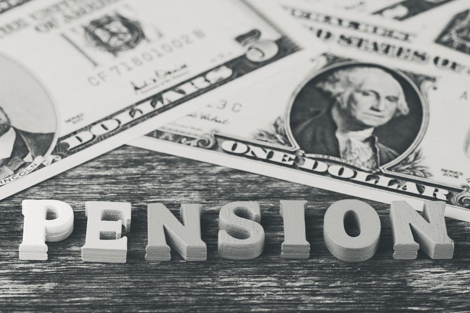 macro of the word -pension- laid with wooden letters beside dollar banknotes, black and white macro photo