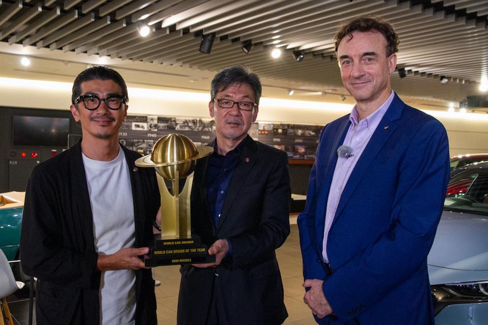 Mazda3 chief designer Yasutake Tsuchida (left) and Mazda's head of global design, Ikuo Maeda (center) receive the World Car Design of the Year trophy from World Car Awards' Peter Lyon at Mazda's HQs in Hiroshima.