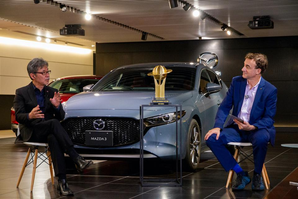 Maeda and Lyon discuss the winner's design in front of the Mazda3.