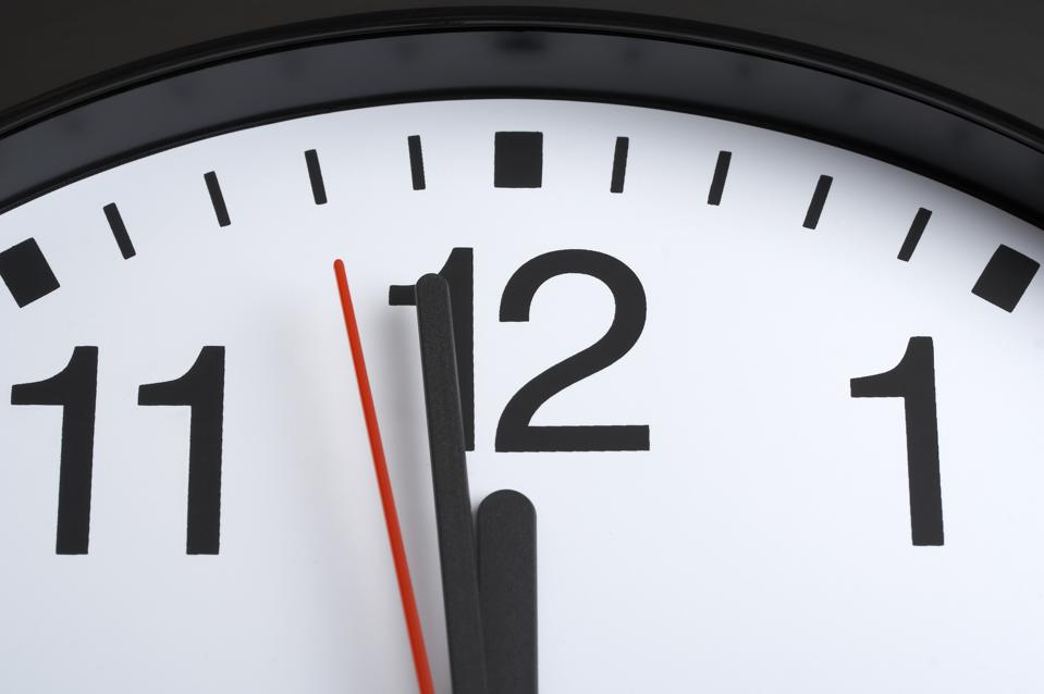 A clock, with the hands at one minute to twelve.