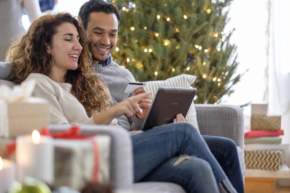 Couple shopping with digital tablet on sofa