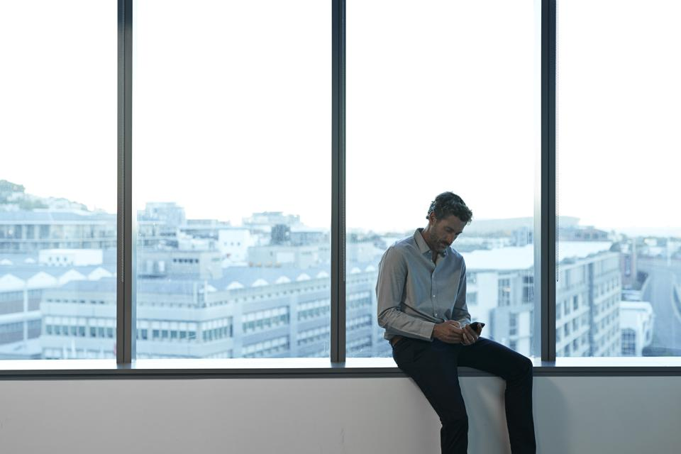Businessman sitting in big windows in office space, checking smartphone