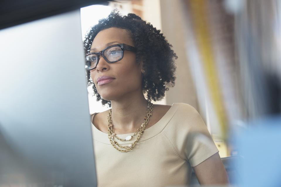 Mixed Race businesswoman working at computer