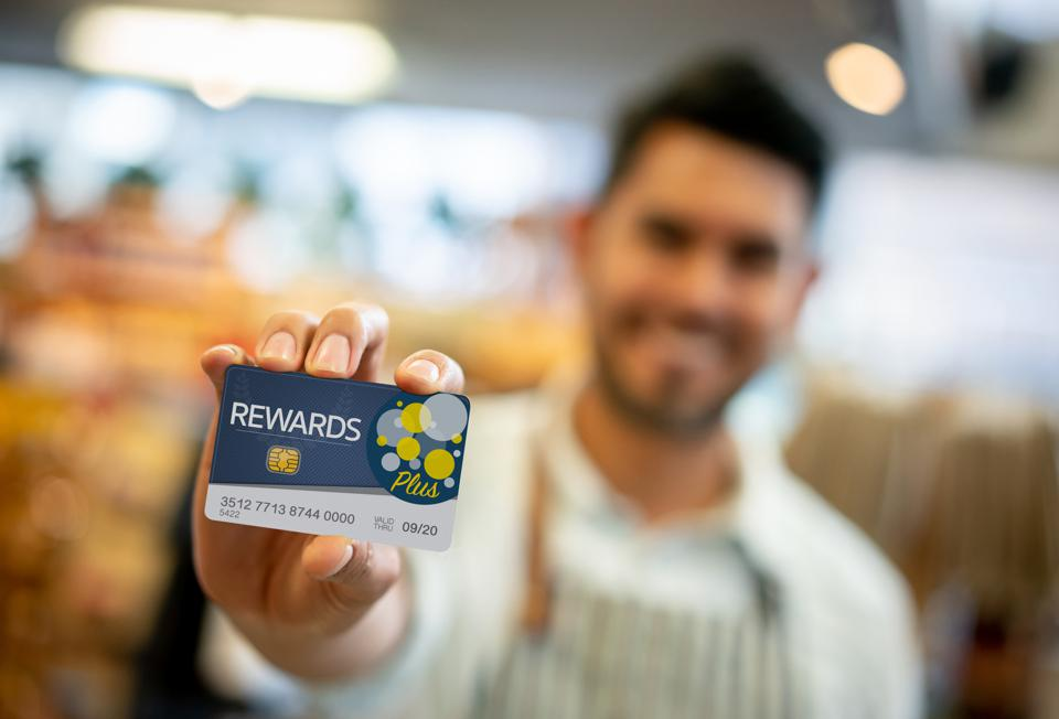 Salesman at a grocery store holding a loyalty program card up front