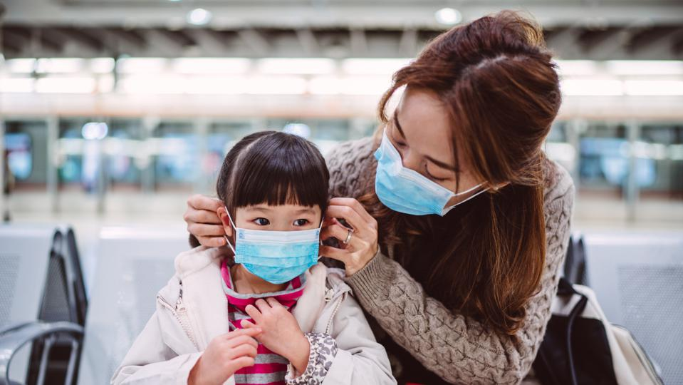 Mom helping her daughter to wear medical face mask on train platform