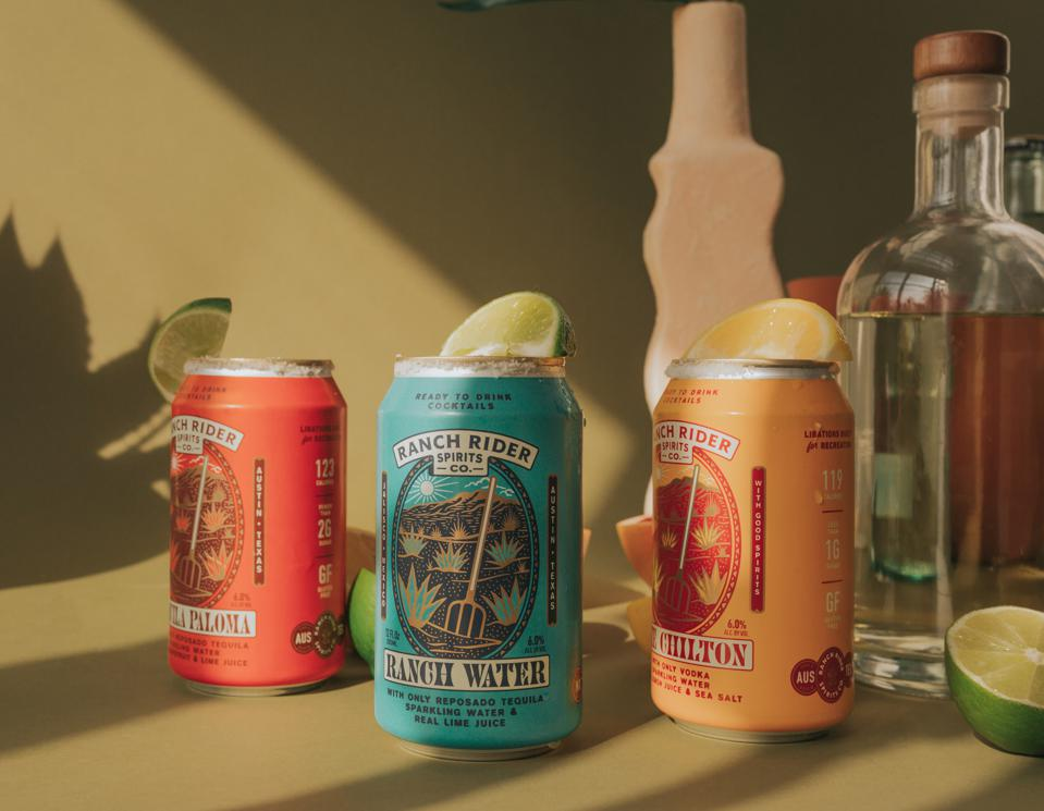 Cans of Ranch Rider cocktails with lime wedges