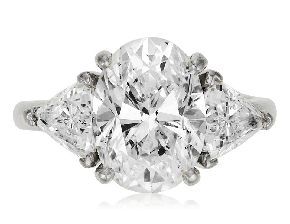 A 4.80-carat oval diamond mounted on a platinum ring and flanked by two diamonds