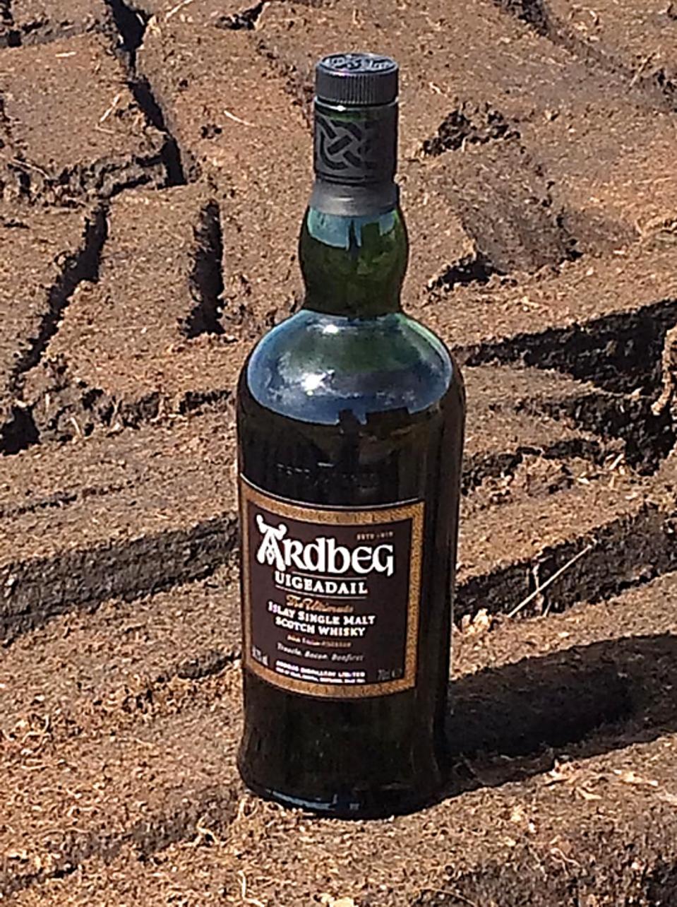 A Bottle of Ardbeg Uigeadail surrounded by newly harvested bricks of peat on Islay