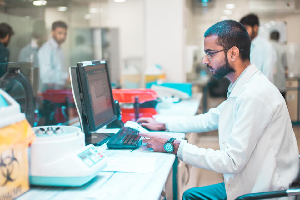 A paramedic working on computer in a medical lab