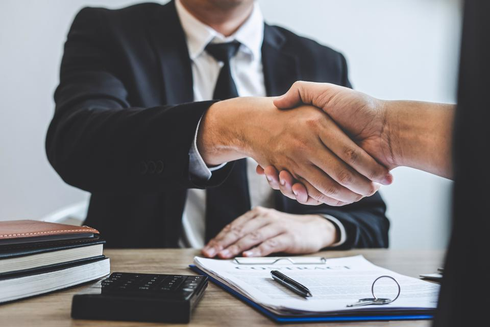 Cropped Hands Of Real Estate Agent Giving Handshake To Customer In Office
