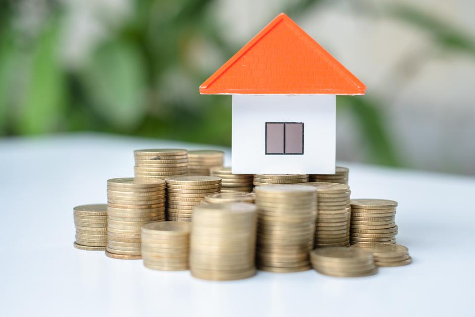 House and coins in the hands of investors.Orange roof house.Save money for buying a new home and borrowing money to plan the real estate investment in the future.There is space for entering text.