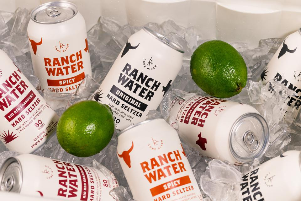 cans of Lone River Ranch Water on ice with fresh limes.