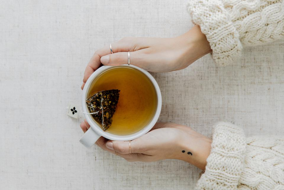 A cup of tea made with an Art of Tea teabag sachet.