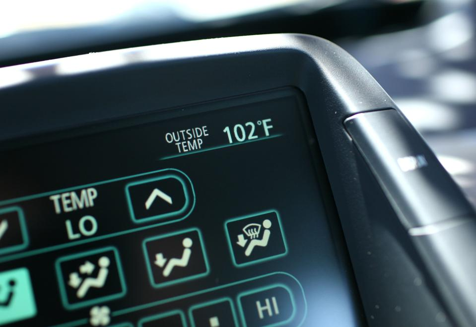 Dashboard thermometer registers 102 degrees outside.