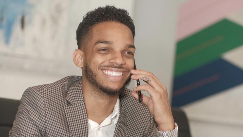 Photo of a young entrepreneur smiling and talking on a phone.