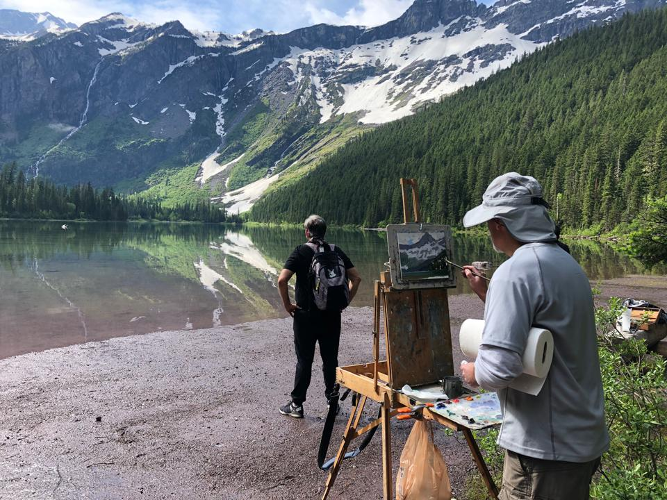 Hiker and painter on the shore of Avalanche Lake, Glacier National Park, Montana.
