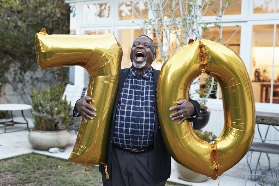 Man with number 70 balloons laughing in backyard