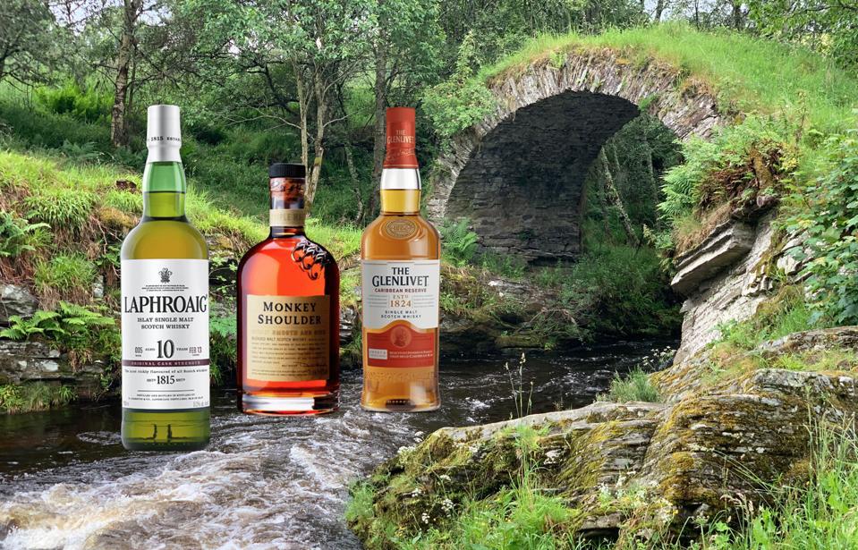 Laphroaig 10, Monkey Shoulder, The Glenlivet Scotch whiskies sit atop a Scottish burn.