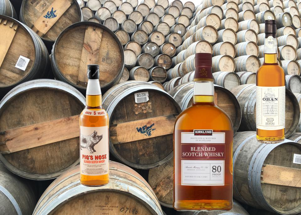 Three large bottles of scotch, Pig's Nose, Kirkland and Oban 14, sit atop scotch barrels