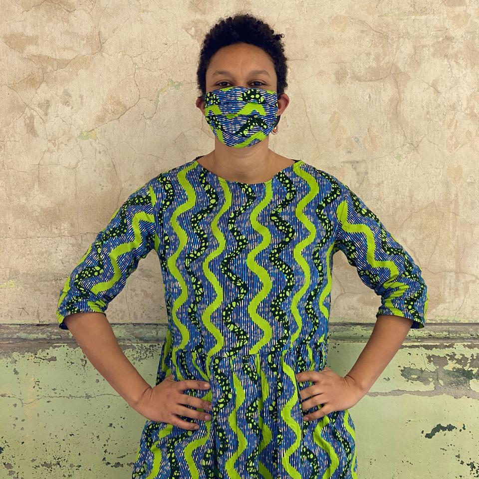 Designer Dinzi Amobi avec masque et robe en tissu imprimé wax africain
