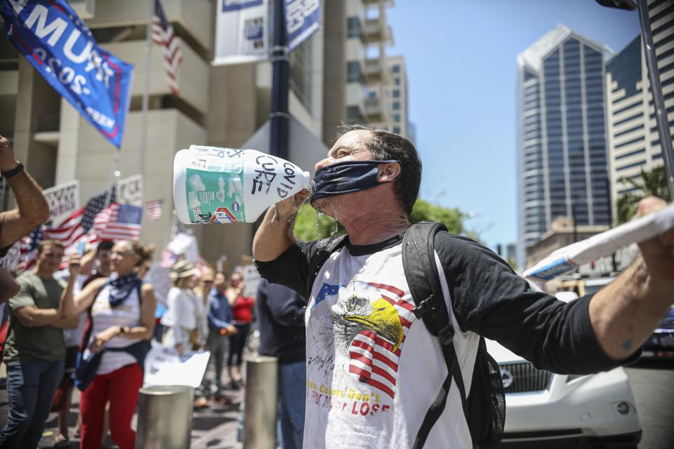 Anti-'stay-at-home' protestor drinks water from a bottle of bleach labelled 'COVID CURE'.