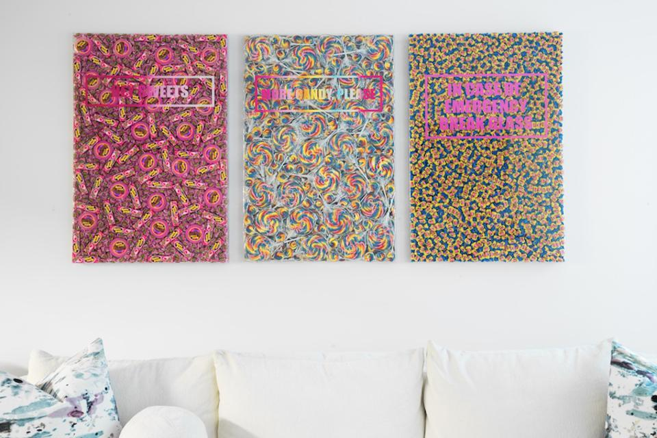 Three pieces of candy art above a white sofa