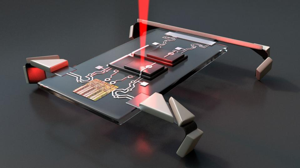 A circuit board with legs is hit by a laser.