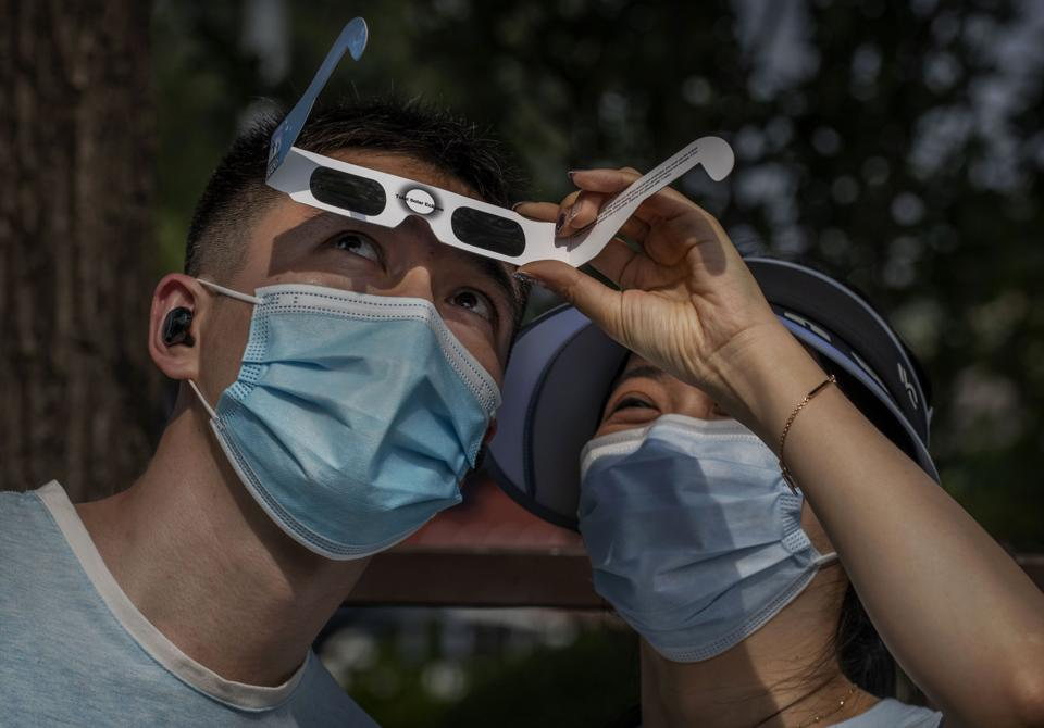 Chinese couple wear protective masks to prevent COVID-19 as they look through protective glasses while watching the sun during the annular solar eclipse outside the Forbidden City on June 20, 2020 in Beijing, China. (Photo by Kevin Frayer/Getty Images)