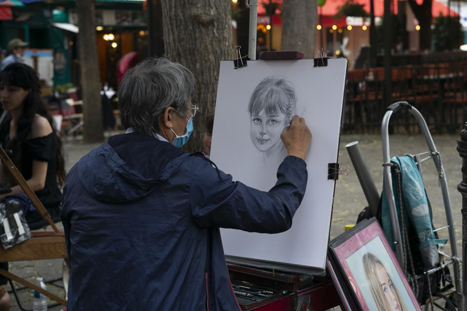 Tourism In Paris amid Covid artist in Montmartre draws wearing mask