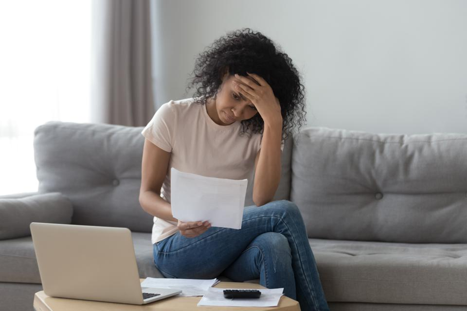 Stressed african woman holding bills worried about bankruptcy bank debt