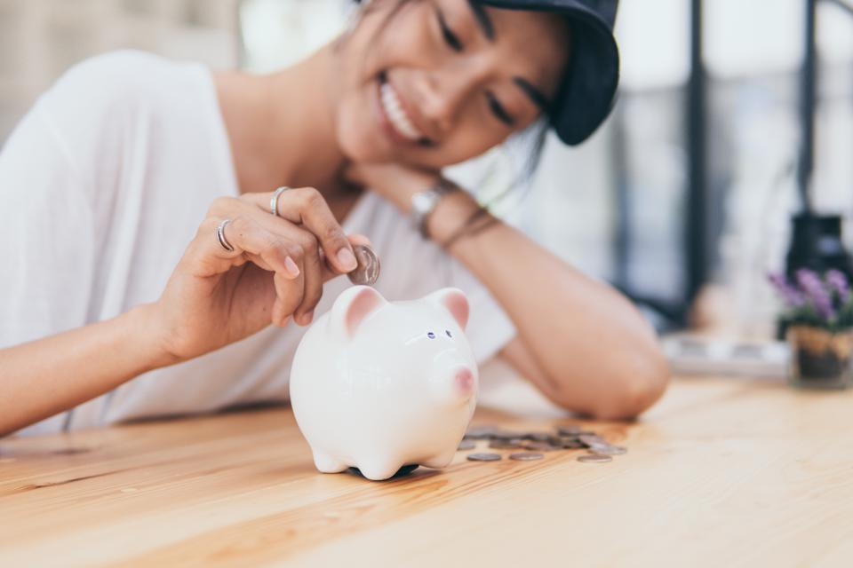 Piggy Bank for saving money.Hand holding money for savings and financial management.