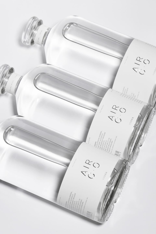 three bottles of air vodka lying flat on white background