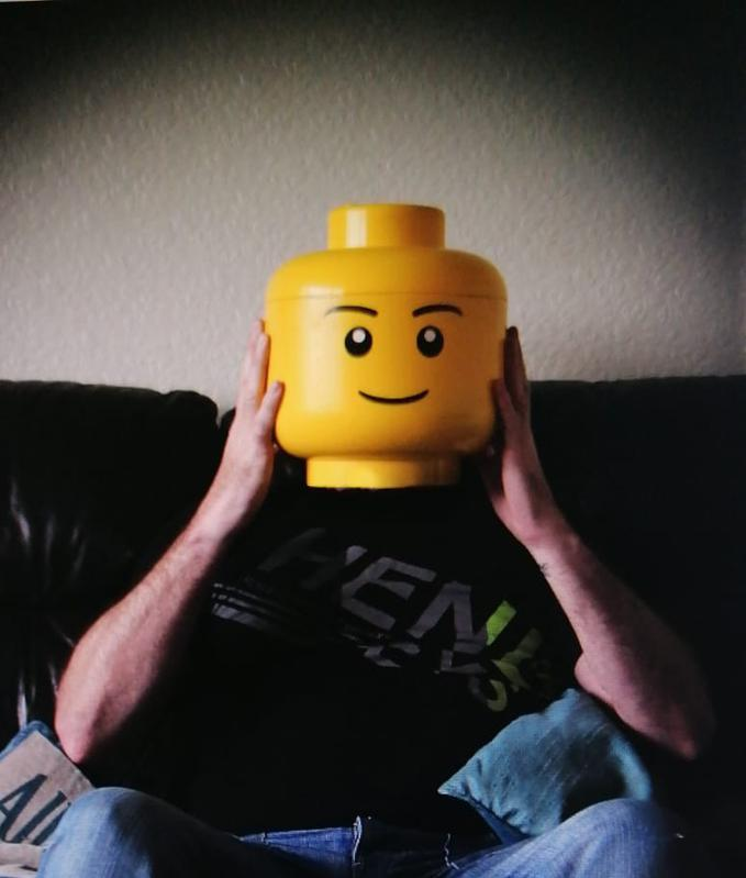 Man sits with lego character head in place of his own head represents masking of individuality