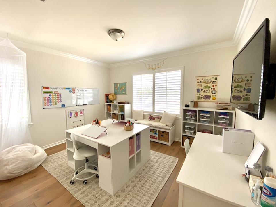 A homeschooling room with two desks, a reading area, a television screen, and cushions.