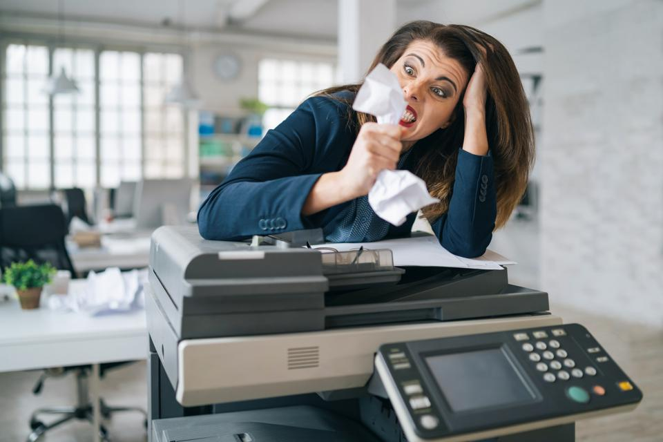 Irritated Business woman standing at printer machine at office