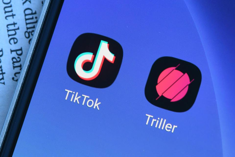 In this photo illustration Triller and TikTok logos are seen...
