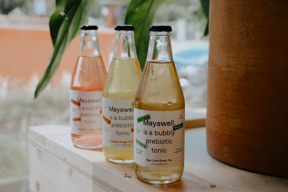 Bottles of Mayawell with tropical background.
