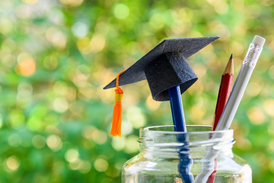 Back to school or graduate certificate program concept : Black graduation cap on a pencil in a bottle. Back to school is the period in which students prepares school supply for upcoming school year.