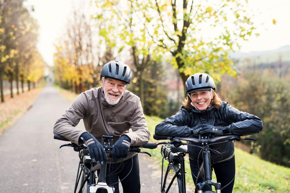 Active senior couple with ebikes standing outdoors on a road in nature.